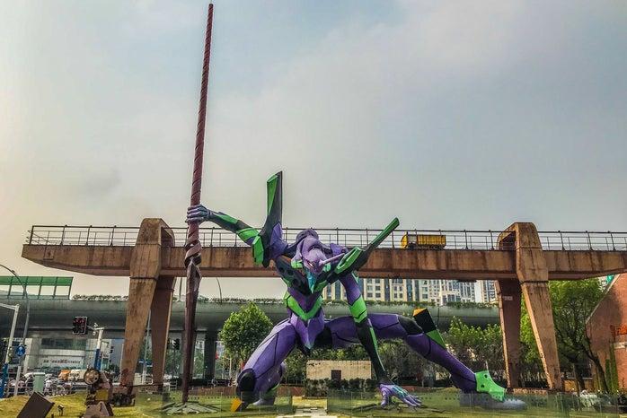Evangelion Sculpture in front of a bridge