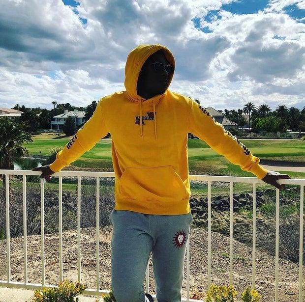 young man wearing yellow sweatshirt