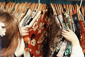 a girl looking through a rack of clothing