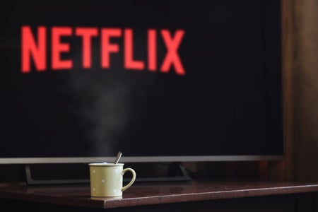 cup in front of tv with Netflix logo