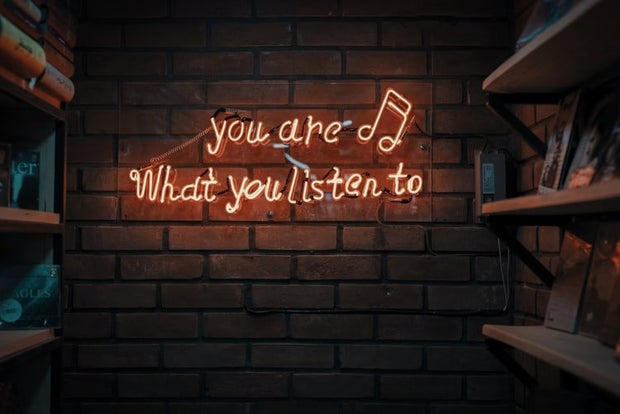 """Orange LED sign that says """"you are what you listen to"""""""