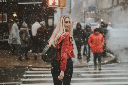 woman walking across the street in the snow