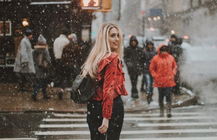 woman walking across the street in the snow