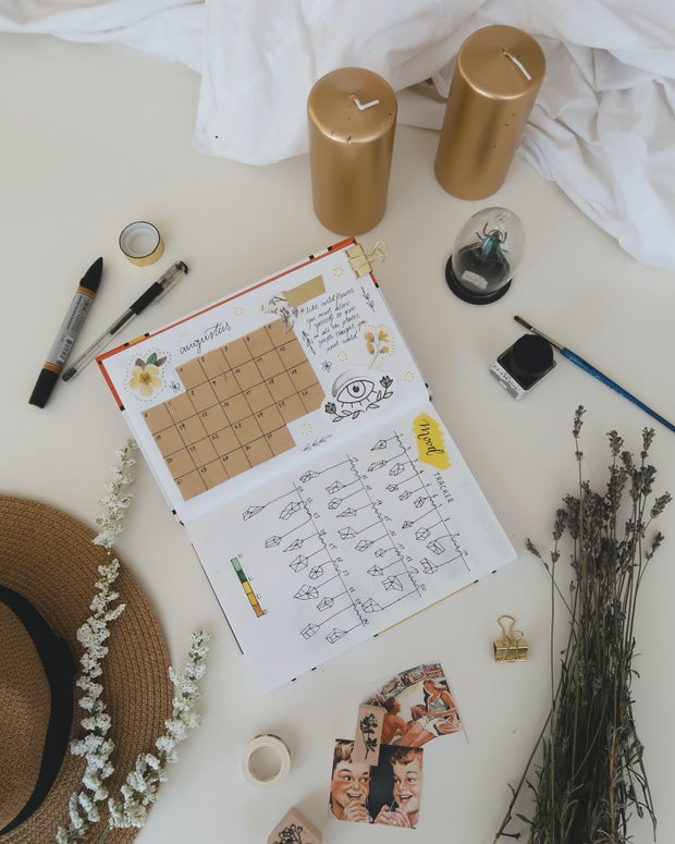 bullet journal with two gold pillar candles