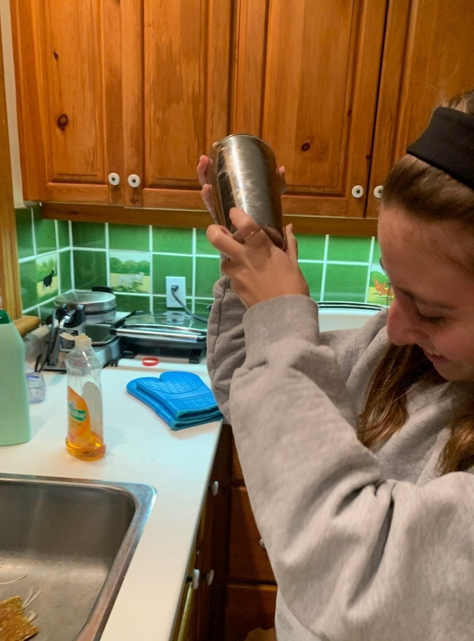Girl shaking cocktail shaker in front of sink in kitchen; pictured are Rachel Alter, Sasha Folgoas and Daphna Roytblat