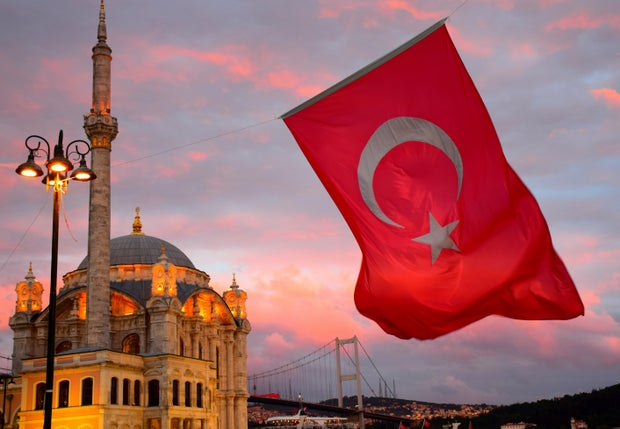 Turkish flag waving in front of a mosque