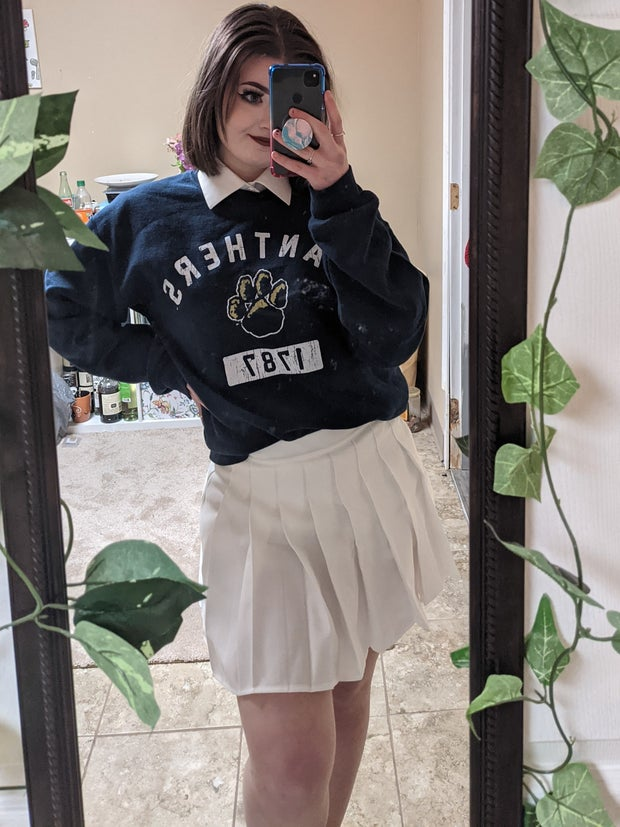 Mirror selfie to show a preppy way to style a tennis skirt