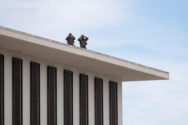 Two law enforcement officers stationed on the roof of the new Florida Capitol Building