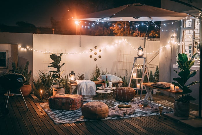patio with ottomans, tables, chairs, and lights