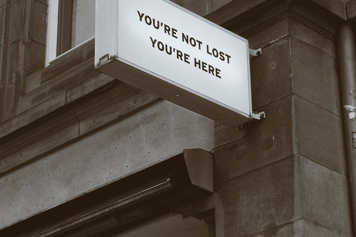 """sign on the side of a building saying """"YOU'RE NOT LOST YOU'RE HERE"""""""