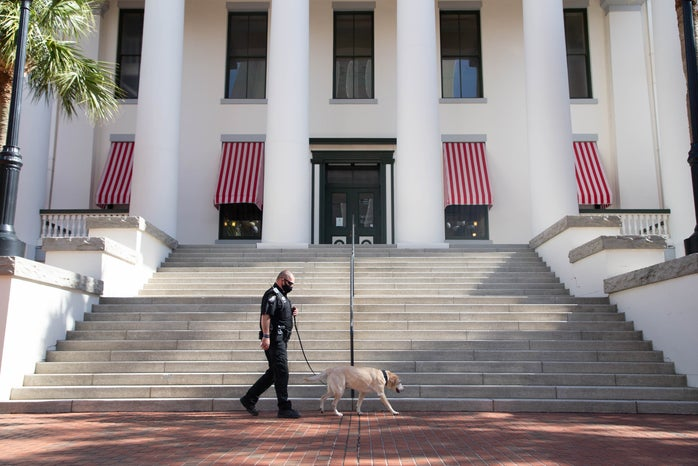 Law Enforcement Officer walking a k-9 in front of the Historic Old Florida Capitol building