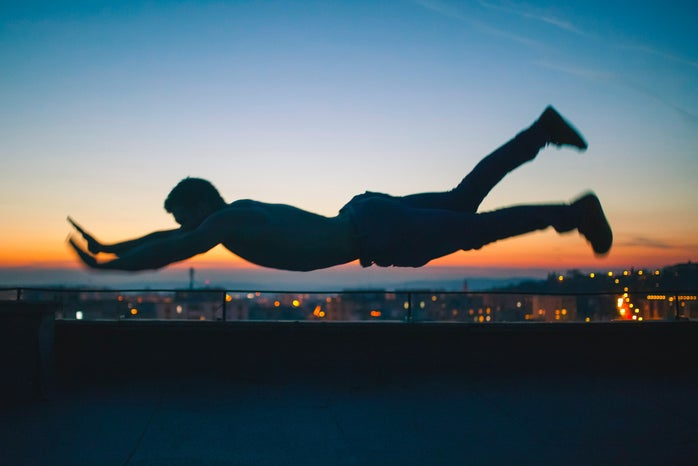 photo of a man hovering horizontally in front of a city scape
