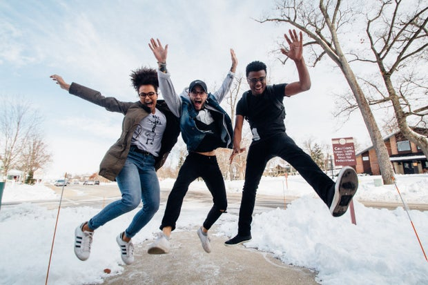 Three people jumping joyfully on snowy day
