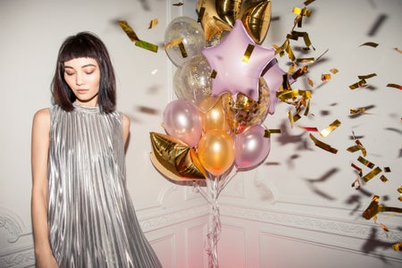 woman wearing a silver pleated dress standing next to balloons