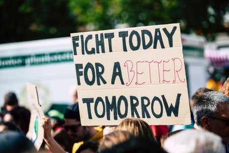 "person holding a sign that says ""fight for a better tomorrow"""