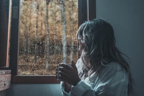 woman in white long-sleeve shirt looking out a rainy window