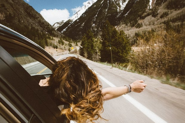 woman with hands out window of car