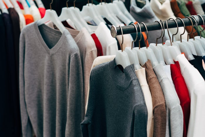 Multiple clothing racks with clothes on hangers