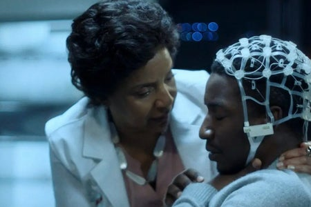 Still from Black Box; Specifically the image of Nolan with the EEG cap on and the doctor, Lillian, speaking to him.