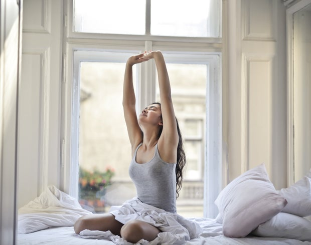 woman sitting on a white bed in front of a window while stretching