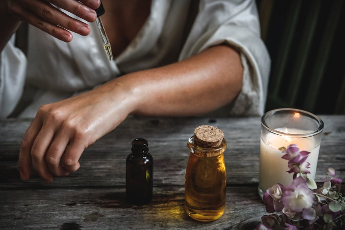 Woman is putting oil on her skin while next to a candle and flowers