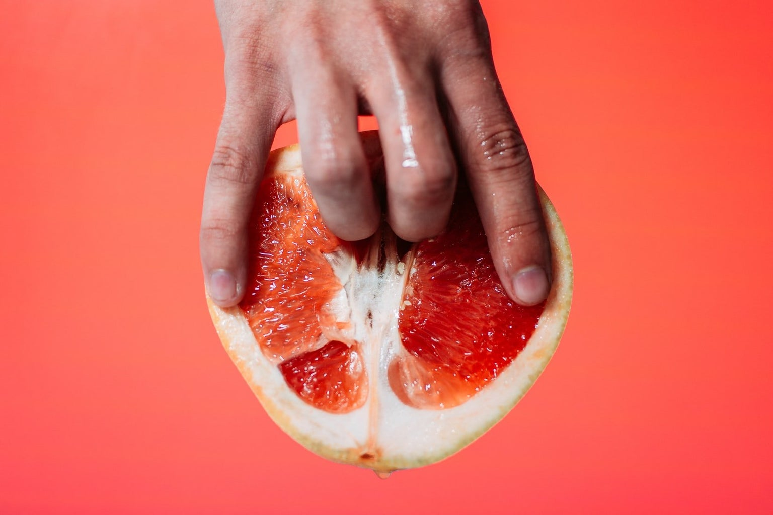 person holding red pomelo fruit