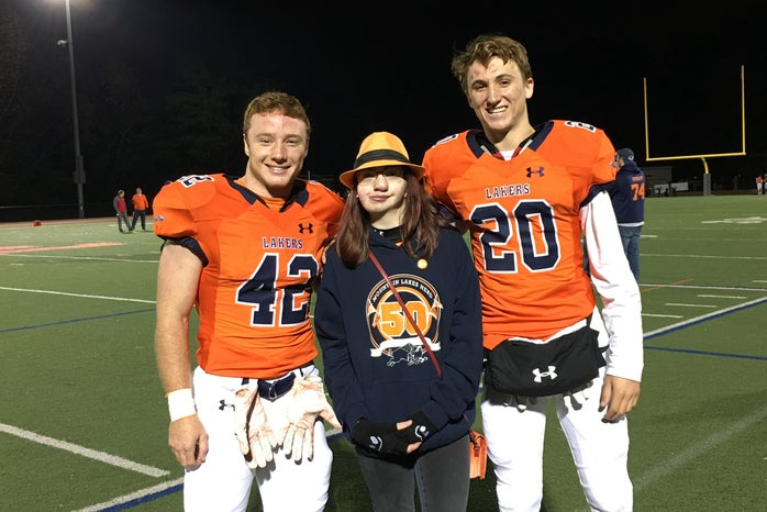 Girl in between two High School Football players