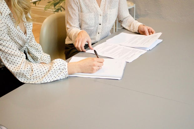 two women sitting at table signing papers