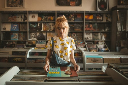 woman in a record store wearing a lemon shirt