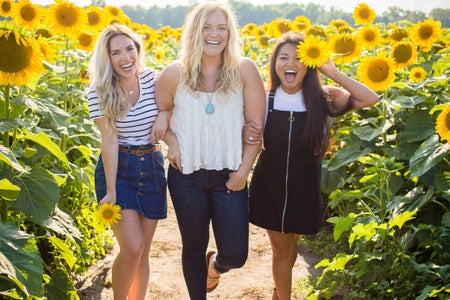woman friends standing in a sunflower field