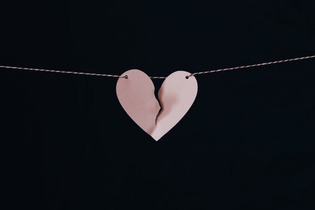 A torn pink paper heart strung on white string with a black background.