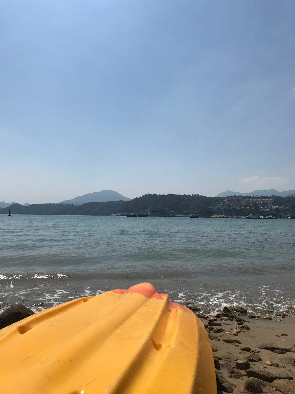 a kayak turned upside down on the beach, an island and clear blue skies in the background