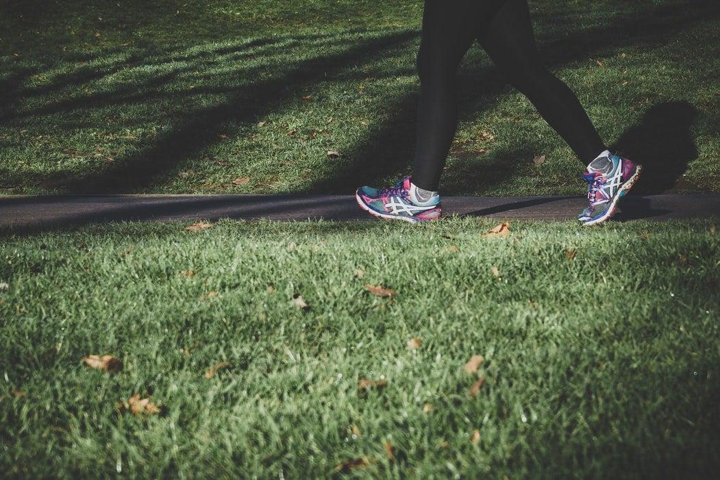 Person running on a narrow path between fields of grass