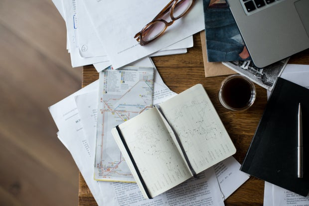 close up of desk with laptop, books, papers and coffee mug