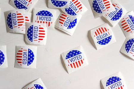 """Lots of """"I voted"""" stickers are scattered on a table."""