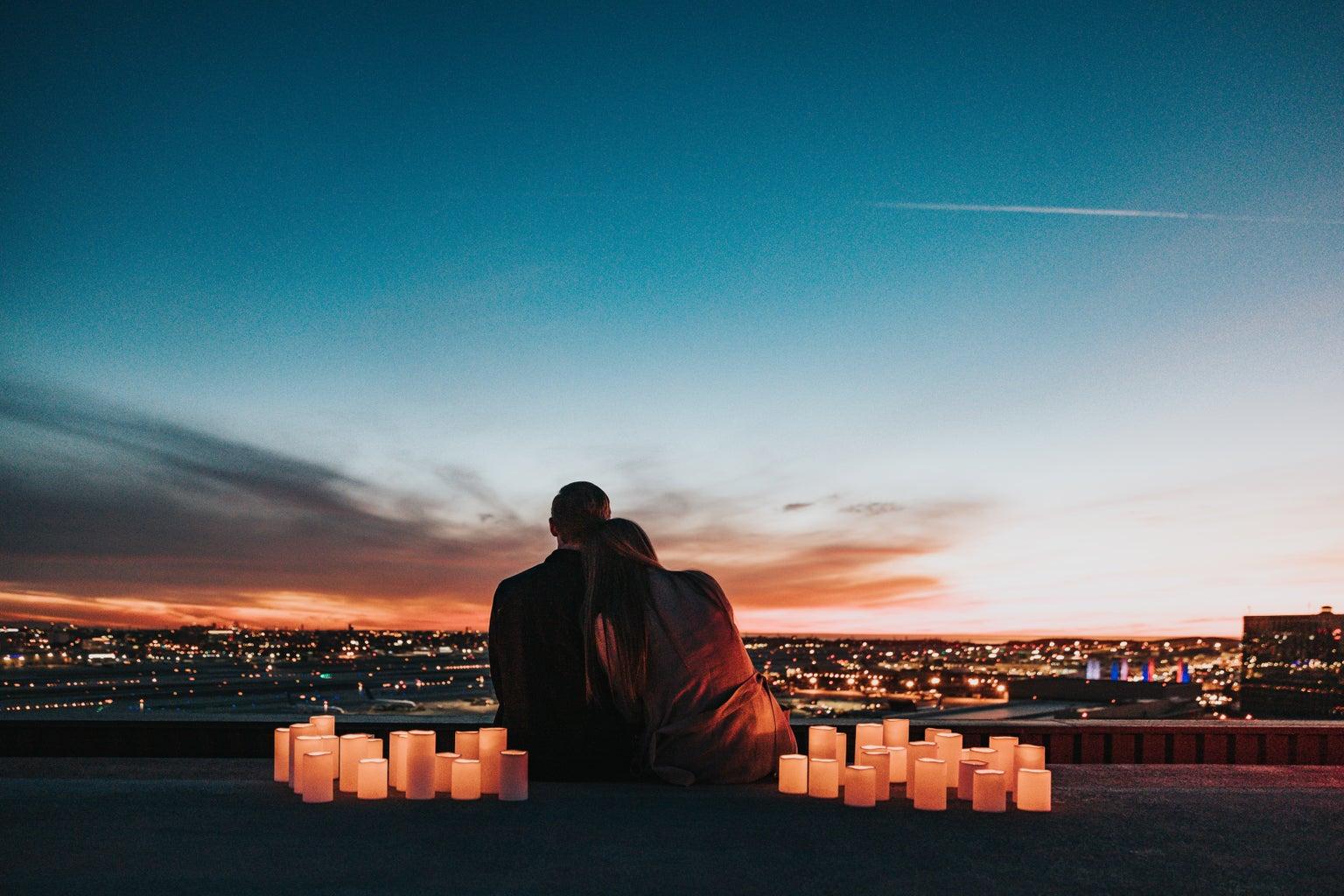 Couple sitting next to lights watching sunset