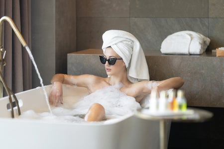 woman wearing sunglasses in bath tub