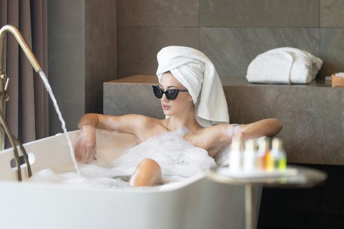 woman wearing sunglasses in bath tub