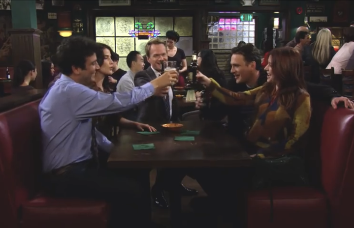 How I Met Your Mother characters raising glasses in a bar