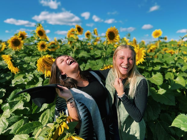 two girls smiling and laughing in a sunflower shield sheaffer