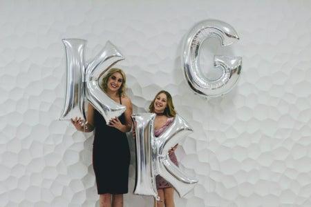two women holding KKG balloons
