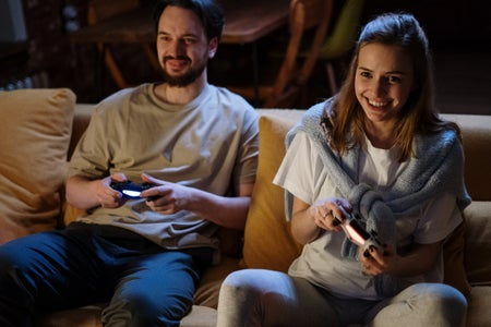 A girl and a guy sitting on a couch and smiling with video game controllers in their hands.