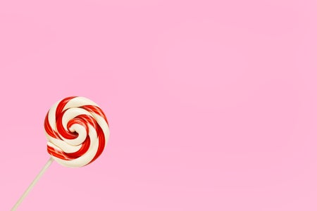 red and white striped lollipop on pink background