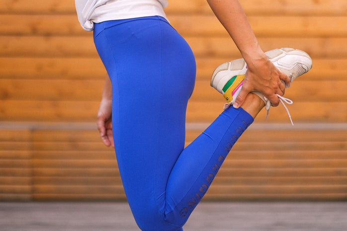 woman in white shirt and blue leggings