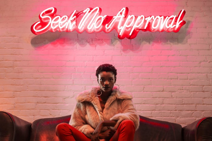 Seek No Approval. A neon light says it all as a model poses beneath.