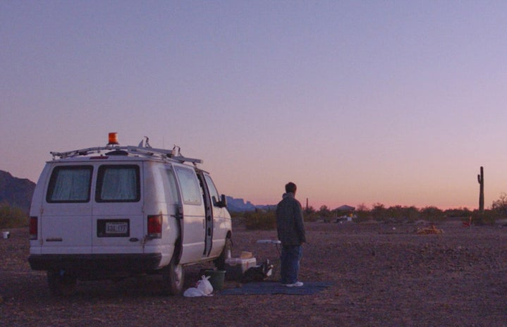 woman standing in front of a white van with her back against the camera, gradient purple sunset in the background