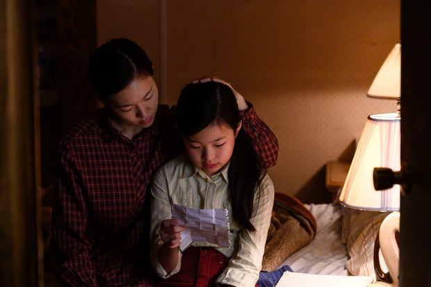Monica Yi and her daughter Anne sitting on a bed and reading a note together.