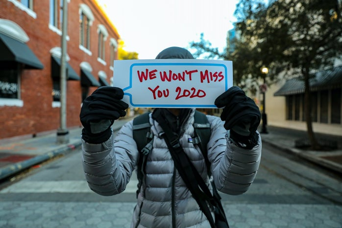 someone holding up a card saying we won\'t miss you 2020