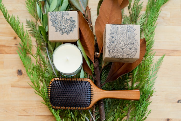 brown wooden hair brush beside white round pate on brown wooden table