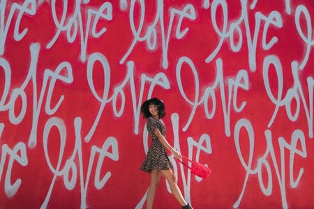 girl in front of love wall